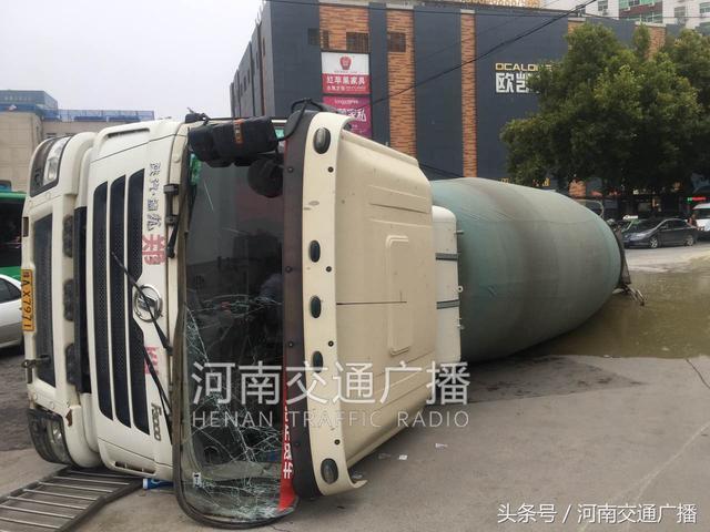 郑州一水泥罐车轮胎陷入大坑,侧翻躺路上!