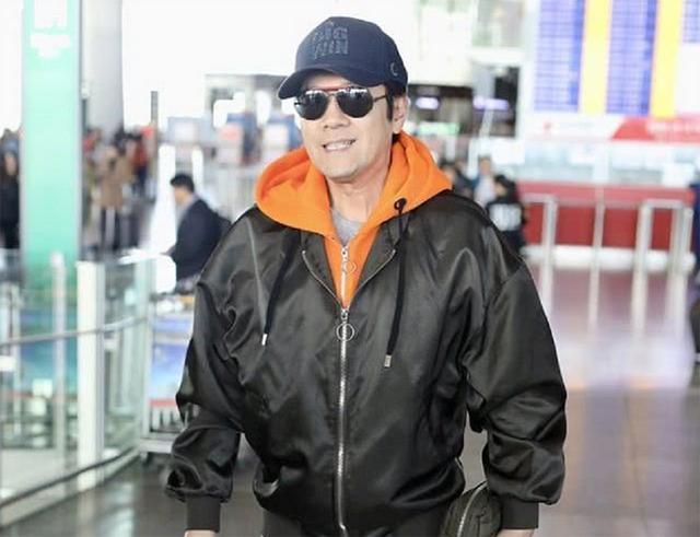 蔡国庆穿印花T恤走机场,下搭白裤清爽减龄,53岁大叔变长腿欧巴