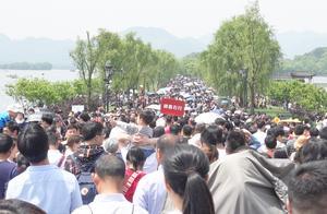 杭州西湖来了一群老年游客,吹拉弹唱很欢乐,大伯嘴上吹的是什么