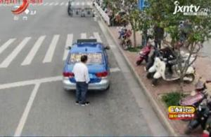 """广西南宁:的士违停遇上无人机 的哥玩起""""人肉挡车牌"""""""