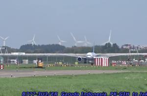 机场的不远处好多风车发电机,南航的货机波音777跑道起飞