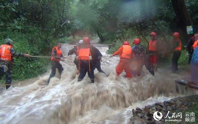 云南:强降雨致29名游客被困 消防官兵山洪中搭人墙救出