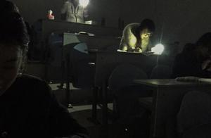 青岛一高校停电 考生在手机电筒灯光下答卷