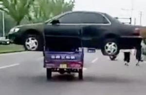 史上最牛操作!男子嫌拖车运费高,竟开三轮车扛轿车