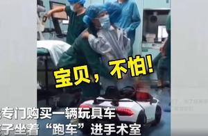 医院用玩具车接孩子进手术室,孩子坐在车上不愿下来