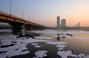 """印度亚穆纳河因污染出现白色有毒泡沫 当地渔民在""""云海""""中前行"""