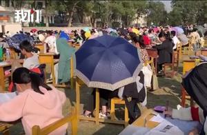 湖南一学校试行在操场上进行期中考试,有学生因太晒撑伞参加