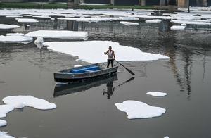 """印度被污染河流漂浮白色泡沫 渔民划船似在""""云海翱翔"""""""