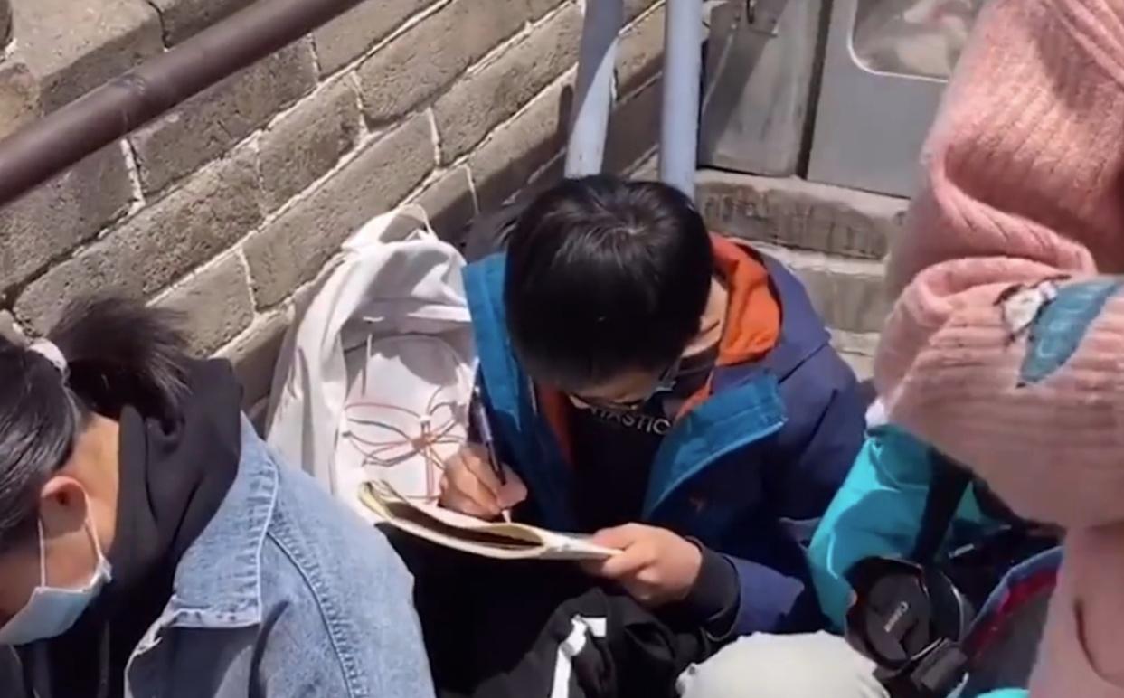 小男孩坐在长城上写作文引发网友热议,景区回应
