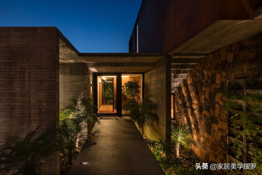 一座由耐候钢和混凝土建造的房子,还带有美丽的绿色篱笆