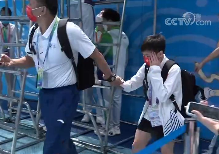 全红婵观战男队比赛!被记者围住,教练迅速将她拉走,挡脸离场