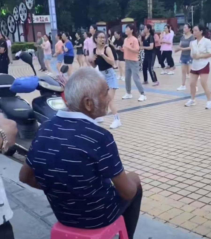 河南信阳大爷带板凳,前排看跳广场舞走红,网友:男人至死是少年